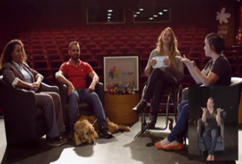 tela com quatro pessoas, uma pessoa surda, uma pessoa cega com cao-guia, tabata contri a entrevistadora, e marisa peres, a interprete de LIBRAS, em um palco de auditorio com as cadeiras ao fundo