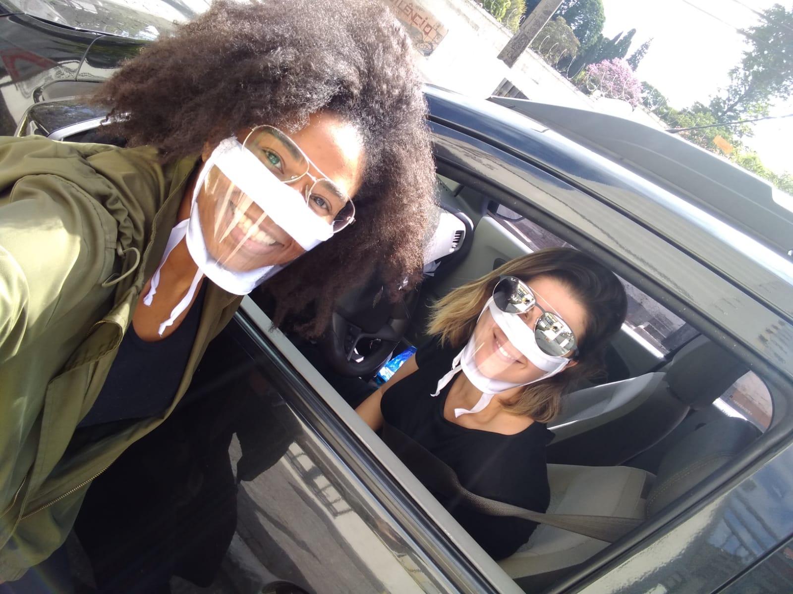 foto de grace, negra vestindo a máscara transparente ao lado de outra colega dentro de um carro