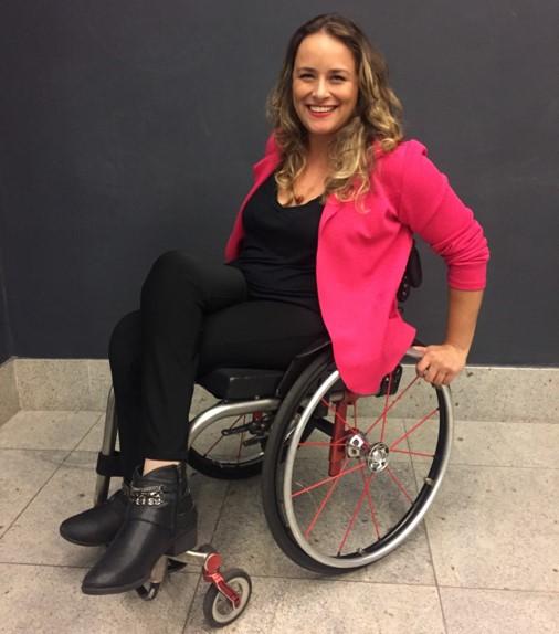 foto de tabata, mulher branca de cabelo longo, sentada em uma cadeira de rodas, com blusa rosa e calça preta