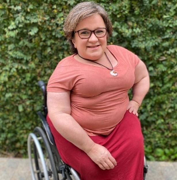 foto de katya, mulher branca com óculos de grau, de cabelo curto, sentada em uma cadeira de rodas, com blusa verde e calça preta