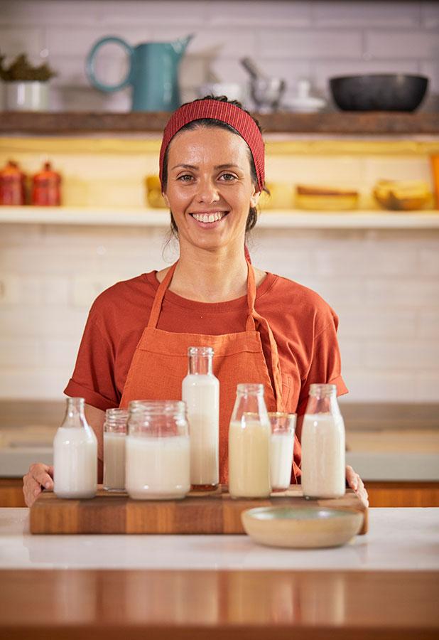 Laura Pires posa com garrafas de leites vegetais, com cozinha ao fundo