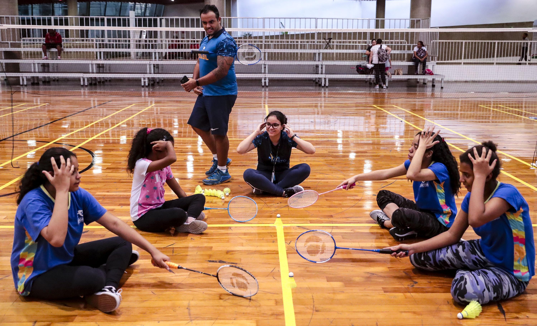Sentadas no chão da quadra, cinco alunas são instruídas pelo professor Andrew Cassiano, que está de pé, em uma aula de badminton no CT Paralímpico