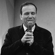 Foto em preto e Branco de Sidney Tobias, um homem branco de cabelo curto. Segura um microfone.