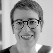 Foto de Ivone Santana em preto e branco. Usa óculos arredondados e tem cabelos curtos. Sorri.