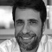 Foto preta e branca de Reinaldo Ferraz, um homem branco de cabelos curtos, lisos, preto e com barba.