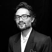Fotografia de Alexandre, um homem asiático de barba, ele usa terno.