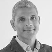 Foto preta e branca de Aurélio Pimenta, um homem moreno claro de cabelos curtos, lisos e grisalhos.