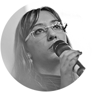 Foto em preto e branco de Talita pagani. Ela usa óculos e segura um microfone.