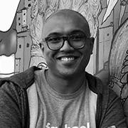 Fotografia de Alexandre, um homem negro de cabelo raspado. Ele está encostado na parede e sorri.