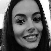 Foto em preto e branco. Milena é uma mulher branca de cabelos longos. Ela sorri.