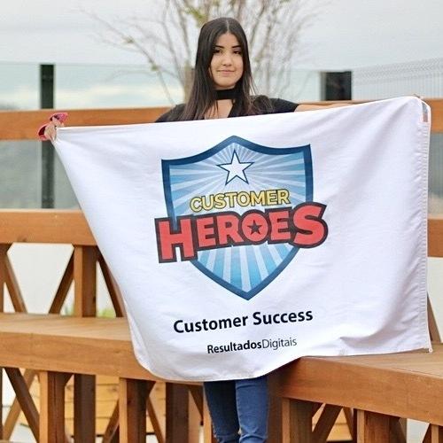 Foto de uma RDoer segurando a bandeira do time de Suporte da RD, o Customer Heroes