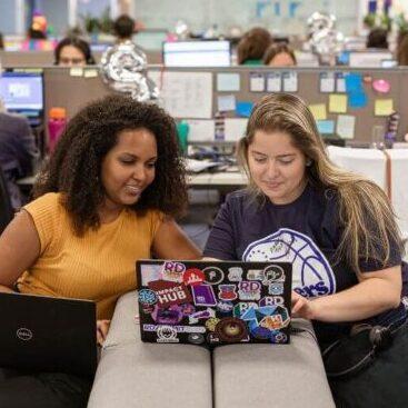 Foto de duas RDoers trabalhando juntas, ambas olhando para o mesma tela de notebook