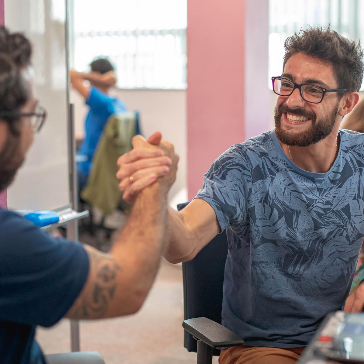 Foto com dois RDoers lado a lado apertando as mãos. Eles são ambos homens brancos, com cabelo curto, óculos e barba.