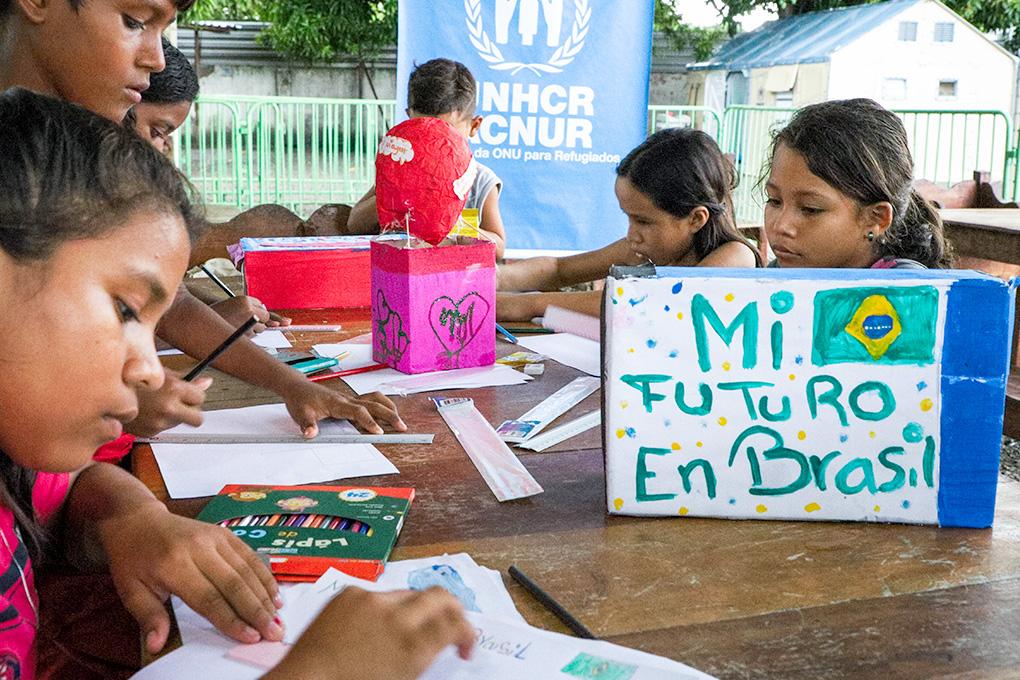 Foto em que aparecem crianças venezuelanas desenhando
