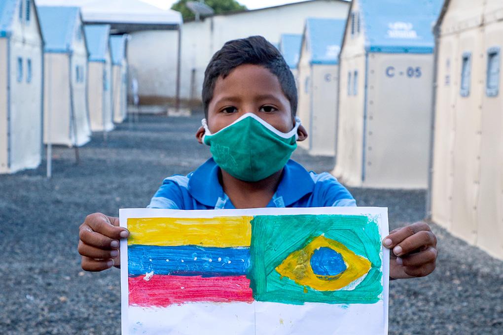 Foto criança de máscara segurando desenho das bandeiras da Venezuela e do Brasil