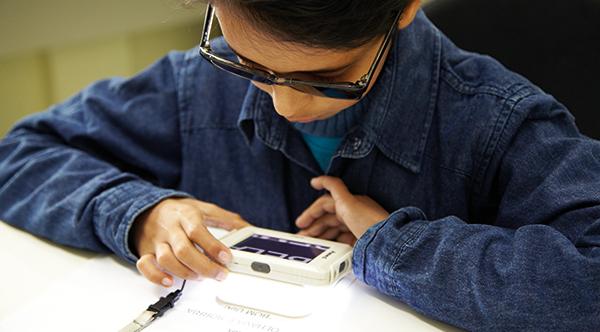 Foto de um menino usando uma lupa eletrônica. Ele tem cabelos lisos, usa óculos escuros, tem pele clara e veste uma jaqueta jeans azul.