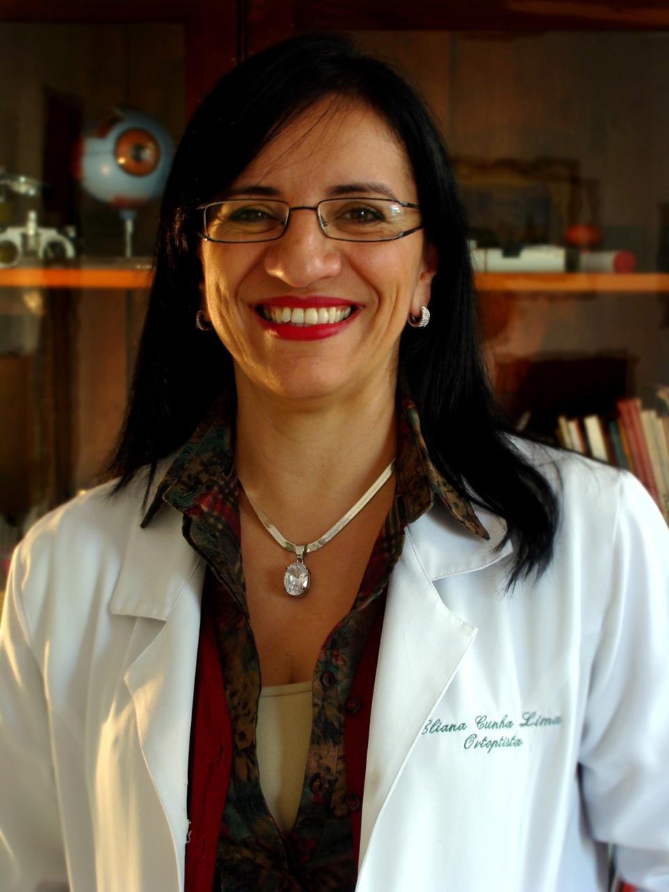 Foto preto e branco de Eliana Cunha. Ela tem pele clara, cabelos lisos na altura dos ombros, usa óculos e colar e está de jaleco.  Ela está sorrindo.