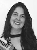 Retrato em preto e branco de Érika Drezza. Ela tem pele clara, cabelos compridos e castanhos  e está sorrindo.