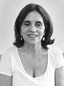 Foto preto e branco de Tânia Resende, retratada do peito pra cima. Ela sua camiseta branca e está sorrindo.